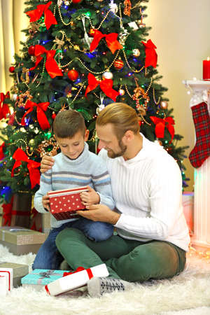Happy father and son at Christmas tree in living room Stock Photo