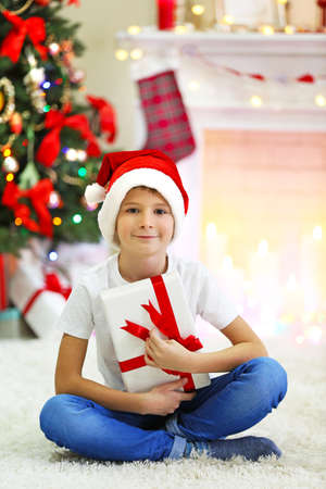Funny boy with gift boxes and Christmas tree on background