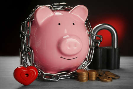 Piggy bank and chains on gray background