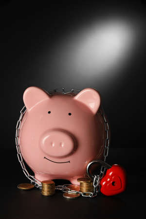 Piggy bank and chains on dark background