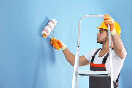 Young worker renewing apartment on wall background 스톡 콘텐츠