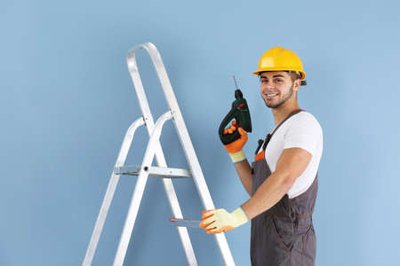 Young worker renewing apartment on wall background Stock Photo