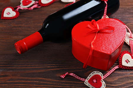 Red wine bottle and gift box on wooden background Stock Photo