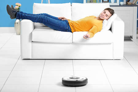 Cleaning concept - automatic robotic  clean the room while man relaxing, close up