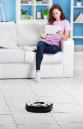 Concepto de limpieza: robot automático que limpia la habitación mientras la mujer se relaja con una computadora portátil, de cerca