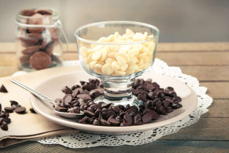 Chocolate morsels in glass bowl on wooden background Stock Photo