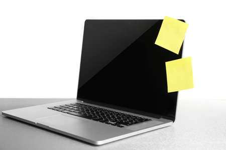 Empty yellow adhesive papers on laptop, on light background