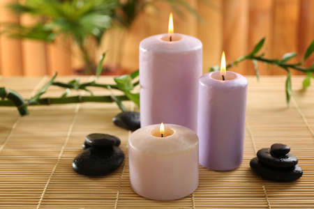 Purple candles with spa stones and bamboo on table