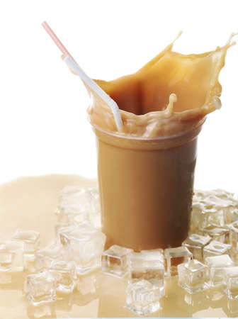 Cup of ice coffee with splashes on table Stock Photo