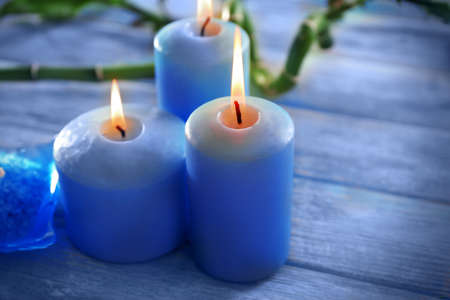 Blue candles with spa salt and bamboo on table