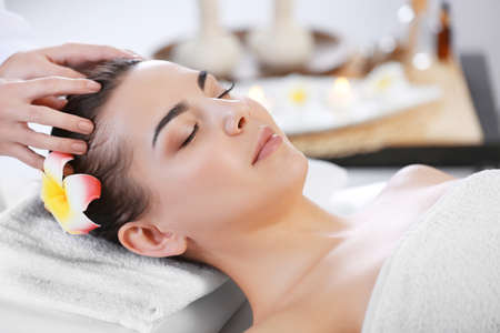 Beautiful young woman relaxing with face massage at beauty spa