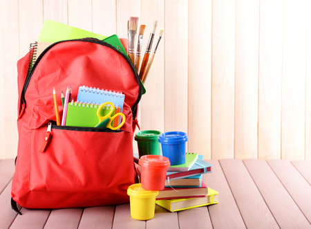 Full of stationery red backpack with colourful paints on wooden table