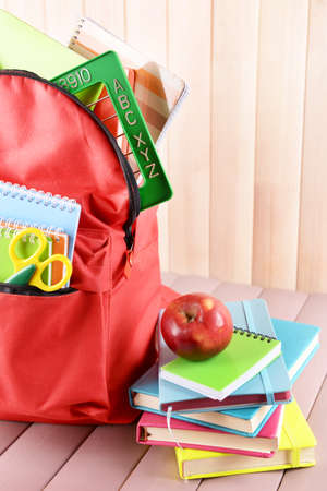 Full of stationary red backpack and pile of books with apple on top on wooden table Stock Photo