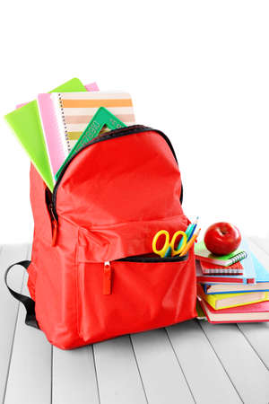 Full of stationary red backpack and pile of books with apple on top on wooden table against white background