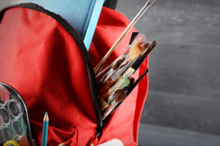 Red backpack full of stationery on blue wooden background, close up Stock Photo