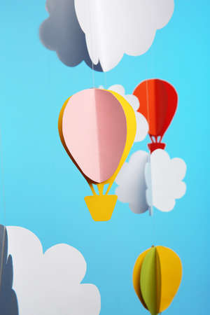 Paper clouds and airship on blue background Banque d'images