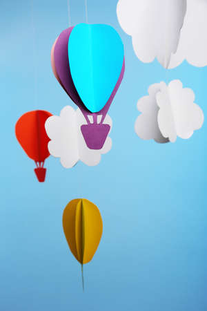 Paper clouds and airship on blue background Stock Photo