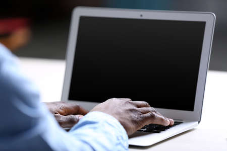 African American businessman in blue shirt working on laptop, close up