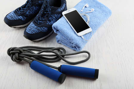 Sport shoes, towel and smart phone on wooden background