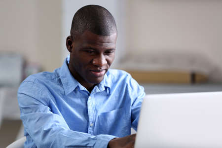 African American businessman in blue shirt with laptop, close up