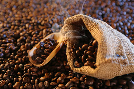 Sackcloth bag with coffee beans on coffee beans background