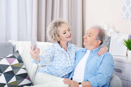 Happy mature couple taking photo of their self with mobile phone at home Stock Photo