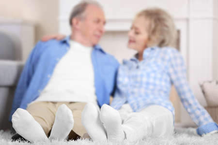 Mature couple sitting together on a floor at home Stock Photo