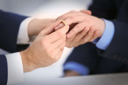 A groom placing the ring on another mans finger