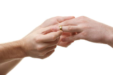 A groom putting a wedding ring on another man's finger isolated on white