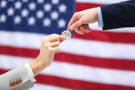 A groom giving a condom to another man on American flag background