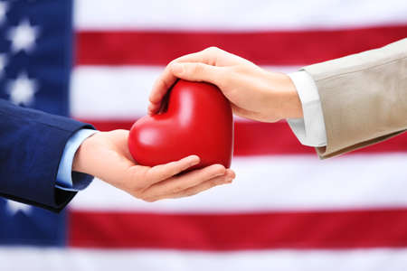Two homosexuals holding heart in their hands on American flag background