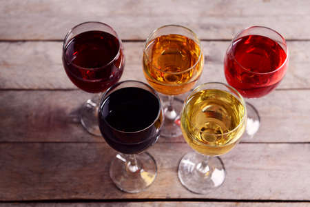 Glasses with wines of different colors on a wooden table
