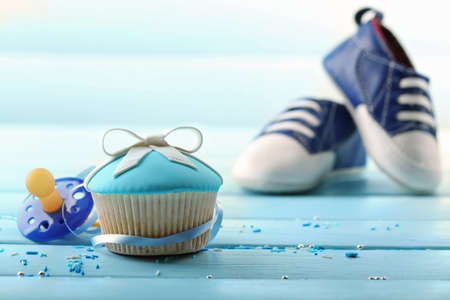 Tasty cupcake with bow and baby shoes on color wooden background