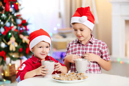 Two cute small brothers eating cookies on Christmas decoration background Stock Photo