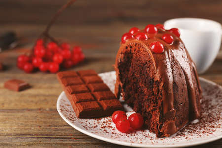Piece of chocolate cake with snowball tree berries on a table