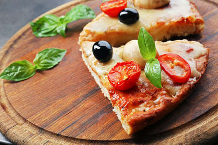 Slices of tasty pizza on round wooden board, close up Stock Photo