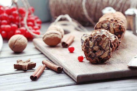 Chocolate salami with walnuts and red berries on a table, close up