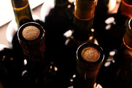 Stapel von Weinflaschen auf hölzernem Hintergrund, Aufwärtsansicht. Nahaufnahme