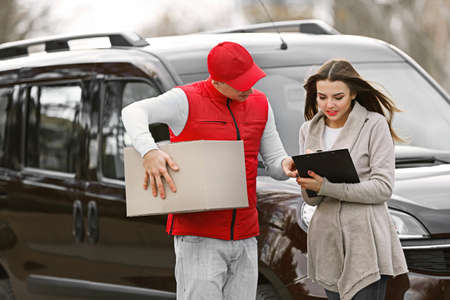 Delivery man and attractive young woman receiving a package, near the car outdoors