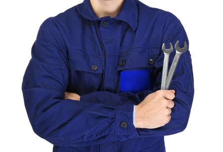 A repairman with crossed arms holding wrenches, on white background, close-up Stock Photo