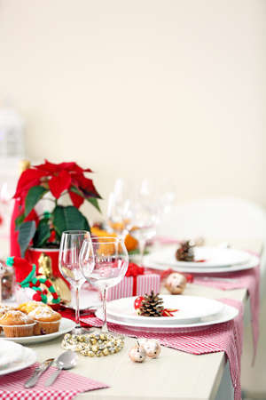 Christmas table setting with holiday decorations on light background