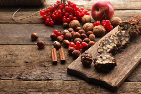 Chocolate salami on a chopping board over wooden background Stock Photo