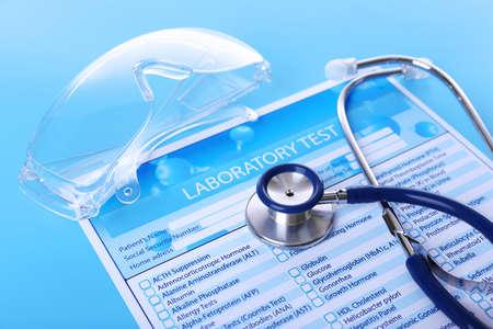 Laboratory test list, stethoscope and eyeglasses on blue background, close up Stock Photo