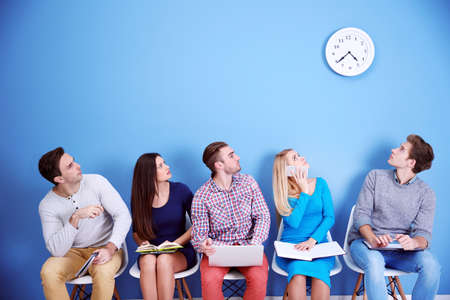 Young people sitting on a chairs and looking at the clock in blue hall Stock Photo
