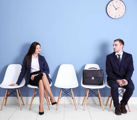 Young businessman and businesswoman sitting on a chairs in blue hall