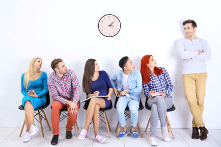 Young people sitting on a chairs and looking at the man in white hall Stock Photo