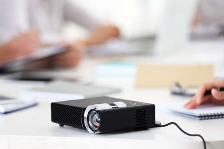 Black projector on white table for business presentation in the foreground Foto de archivo