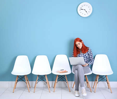 Young redhead girl sitting on a chair and using laptop in blue hall Foto de archivo - 95607592