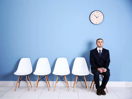 Young businessman sitting on a chair in blue hall