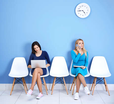Young girls sitting on a chairs in blue hall